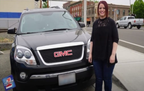 Smiling young lady standing next to her GMC vehical with a collision 1 logo overlay